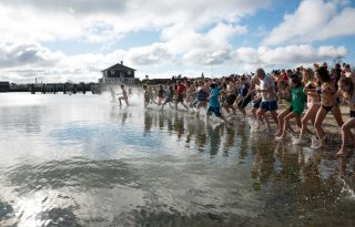 A crowd of partisipants entering the water for the Cold Turkey Plunge