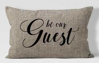 "pillow with written words ""be our guest"""