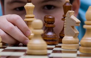 child peeing at chessman