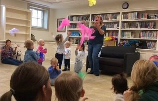 Lizza Obremski tossing handkerchiefs with children