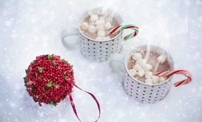 Two mugs of hot chocolate in the snow.